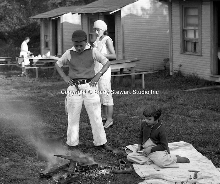 Markleysburg PA:  Stewart family camping out at the Lone Star Inn's cabins near Youghiogheny Lake.  Brady Jr. and Sally Stewart putting out a campfire in front of the rental cabin, the family having lunch before going to Youghiogheny Lake.
