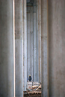 A worker stands among the giant pillars that supports an elevated highway under construction in Shanghai, China. China is currently continuing its massive plans to expand and upgrade its road networks, with heavy emphasis in constructing highways in the remote and less developed western regions...
