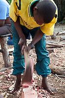 Nungwi, Zanzibar, Tanzania.  Dhow Construction, Boat Building.  Smoothing a Rib using an Adze.