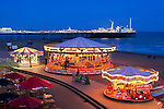 Great Britain, England, East Sussex, Brighton: Nightshot of beachside carousels with Brighton pier illuminated in background