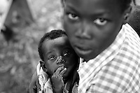 Empowering Victims of War- A young resident holds an infant boy. Canaan Family Farm lends land to displaced people from the Northern conflict to have them learn the benefits of work and empowerment. Rwakayata, Masindi, Uganda, Africa. December 2005 © Stephen Blake Farrington