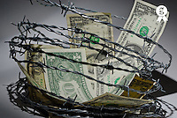 Dollar banknotes surrounded by barbed wire, close-up (Licence this image exclusively with Getty: http://www.gettyimages.com/detail/sb10061763s-001 )