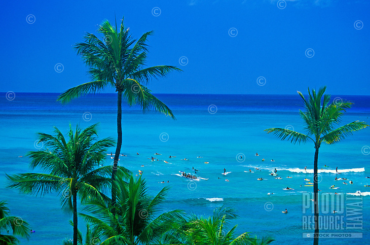 Surfers enjoy riding the waves off renowned Waikiki Beach with it's warm sands, blue waters, resort hotels and swaying palm trees.