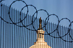Barbed wire and fencing stand in front of the U.S. Capitol ahead of President-Elect Joe Biden's Inauguration on January 19, 2021 in Washington, D.C..  Photograph by Michael Nagle