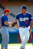 Ivan Rodriguez of the Texas Rangers talks with Mike Scioscia of the Los Angeles Dodgers before a game at Dodger Stadium in Los Angeles, California during the 1997 season.(Larry Goren/Four Seam Images)
