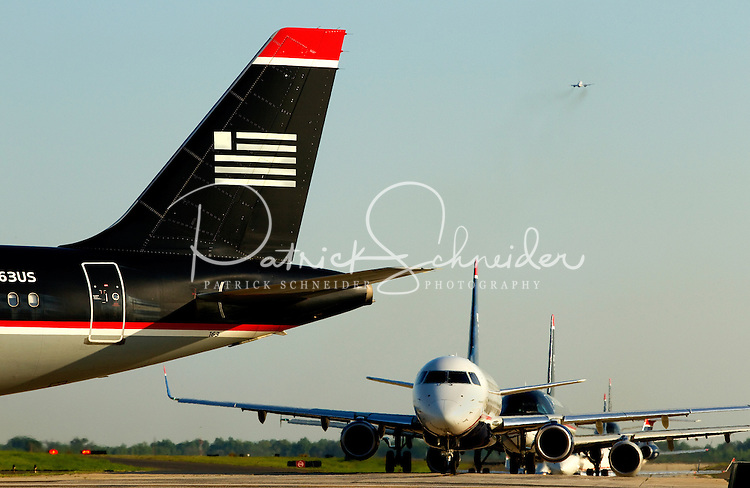 A line of planes wait on the tarmac for permission to take off at Charlotte-Douglas International Airport in Charlotte, North Carolina. Charlotte-based photographer has other images of transportation, airplanes on runways (and taking off and landing) and interior/exterior airport images of Charlotte-Douglas Intl Airport in portfolio.