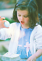 Beautiful young girl smiling wearing a dress and holding an Easter egg.