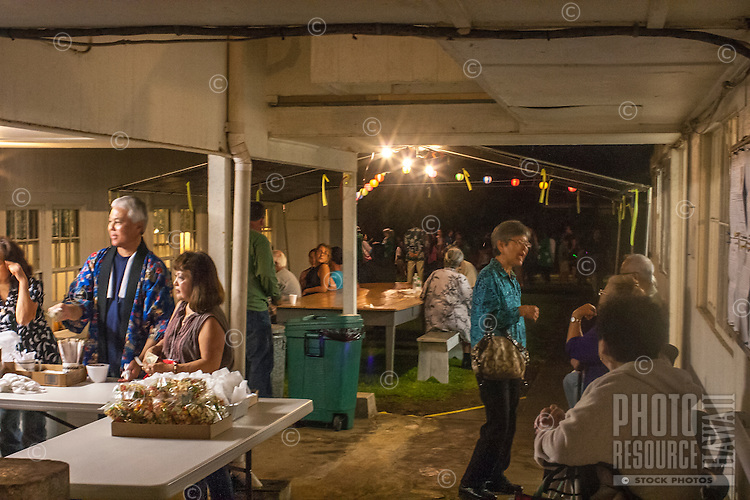 People gather outside to eat, talk and catch their breath at the Hakalau Jodo Mission Bon Dance, Big Island of Hawai'i 2014, where local families come each year to celebrate their ancestors.