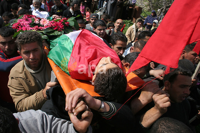 Palestinians carry the body of Fayez Atta,17, during his funeral in the West Bank village of Dir Mishaal, north of Ramallah, Thursday, March 12, 2009 .APAIMAGES PHOTO /Issam rimawi