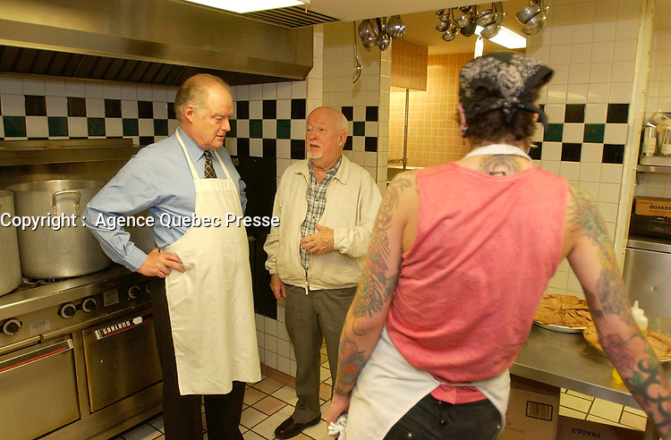 """Montreal, October 27th 2001<br /> <br /> """"Dans la rue"""" founder father Emmett Johns a.k.a. """"Pops"""" (M) gives a guided tour of the   kitchen to  AndrÈ CaillÈ (L ); president and CEO of Hydro Quebec  and honorary chairman of  it's 2001 fundraising campaign, at the organization headquarters located at 1664 Ontario East, in Montreal, CANADA, on Tuesday, November 27.<br /> <br /> CaillÈ served lunch to the young people who use the day centre and those who stop by.<br /> <br /> """"Dans la rue"""", an organization founded in 1988 by father Emmett Johns a.k.a. """"Pops"""" is well known for the services offered by the Roulotte, an emergency shelter and day centre. . This year's goal is to raise $2.5 million to help Montreal's 5,000 young homeless people<br /> throughout the year.<br /> <br /> <br /> Photo by Sevy-IMAGES DISTRIBUTION <br /> <br /> NOTE :  D-1 H original JPEG, saved as Adobe 198 RGB"""