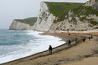 BNPS.co.uk (01202 558833)<br /> Pic: Graham Hunt/BNPS<br /> <br /> What a difference a year makes..<br /> <br /> The windswept beach at Durdle Door in Dorset is virtually deserted today, exactly a year after glorious weather saw thousands flock to the iconic landmark. <br /> <br /> A few stragglers, wrapped up in hats and coats, braved the wind and rain to walk along the beach that became a magnet for sunseekers during last year's pandemic.<br /> <br /> Whilst last year saw temperatures into the mid-20s - way above the average for May - today the thermometer struggled to reach 10C.<br /> <br /> (This picture was taken on 20/5/21)