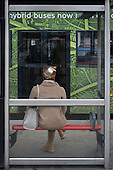 Woman sitting in a bus shelter, Kings Cross, London.