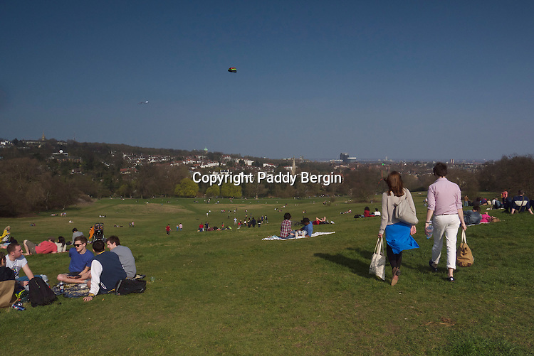 """Kite Hill and picnickers on Hampstead Heath (locally known as """"the Heath"""") is a large, ancient London park, covering 320 hectares (790 acres). This grassy public space sits astride a sandy ridge, one of the highest points in London, running from Hampstead to Highgate, which rests on a band of London Clay. The Heath is rambling and hilly, embracing ponds, recent and ancient woodlands, a lido, playgrounds, and a training track, and it adjoins the stately home of Kenwood House and its grounds. The south-east part of the Heath is Parliament Hill, from which the view over London is protected by law.<br /> <br /> Kenwood House (also known as the Iveagh Bequest) is a former stately home, in Hampstead, London, on the northern boundary of Hampstead Heath. It is managed by English Heritage, and normally open to the public. The house was closed for major renovations from 2012 until late 2013.<br /> <br /> Stock Photo by Paddy Bergin"""