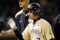 Joey Rodriguez (7) of the Wake Forest Demon Deacons high fives teammates after scoring a run against the North Carolina State Wolfpack at Wake Forest Baseball Park on March 15, 2013 in Winston-Salem, North Carolina.  The Wolfpack defeated the Demon Deacons 12-6.  (Brian Westerholt/Four Seam Images)