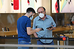 An employee of a computer store attends to a visitor in the Xanadu Shopping Center in Madrid on the day of its reopening during the beginning of Phase 2 of the unconfinement during the health crisis due to the Covid-19 - Coronavirus pandemic. June 8,2020. (ALTERPHOTOS/Ricardo Blanco)