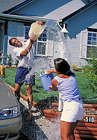 couple having fun and throwing water while washing car in suburban neighborhood. couple.