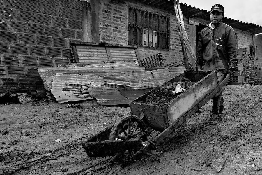 A displaced man from Huila department pushs a wheel barrow in the mud while building a new house in the slum of Ciudad Bolívar, Bogota, Colombia, 27 May 2010. With nearly fifty years of armed conflict, Colombia has the highest number of civil war refugees in the world. During the last ten years of the civil war more than 3 million people have been forced to abandon their lands and to leave their homes due to the violence. Internally displaced people (IDPs) come from remote rural areas, where most of the clashes between leftist guerrillas FARC-ELN, right-wing paramilitary groups and government forces takes place. Displaced persons flee in a hurry, carrying just personal belongings, and thus they inevitably end up in large slums of the big cities, with no hope for the future.