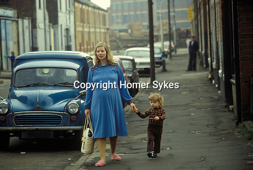 Hull, Humberside. 1980<br /> In conservative blue and wearing her indoor pink slippers, Gillian Carrington seven months pregnant with Sonya and holding two year old Scott's hand; surely a latter day Millais 'Bubbles' model, wanders down Subway Street past a Morris Minor Panel Van on her way to the shops. The Hessle Road area, an inner city working class enclave was home to fishermen and dockworkers. <br /> <br /> The Lord Line building - former trawler company distinctive offices near the Albert Docks are seen in the background.   <br />   <br />    <br /> <br /> .