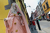 A statue of Santa Muerte (Saint Death) is seen placed on the street close to Zocalo, the historical center of Mexico City, Mexico, 2 May 2011. The religious cult of Santa Muerte is a syncretic fusion of Aztec death worship rituals and Catholic beliefs. Born in lower-class neighborhoods of Mexico City, it has always been closely associated with crime. In the past decades, original Santa Muerte's followers (such as prostitutes, pickpockets and street drug traffickers) have merged with thousands of ordinary Mexican Catholics. The Saint Death veneration, offering a spiritual way out of hardship in the modern society, has rapidly expanded. Although the Catholic Church considers the Santa Muerte's followers as devil worshippers, on the first day of every month, crowds of believers in Saint Death fill the streets of Tepito. Holding skeletal figurines of Holy Death clothed in a long robe, they pray for power healing, protection and favors and make petitions to 'La Santísima Muerte', who reputedly can make life-saving miracles.
