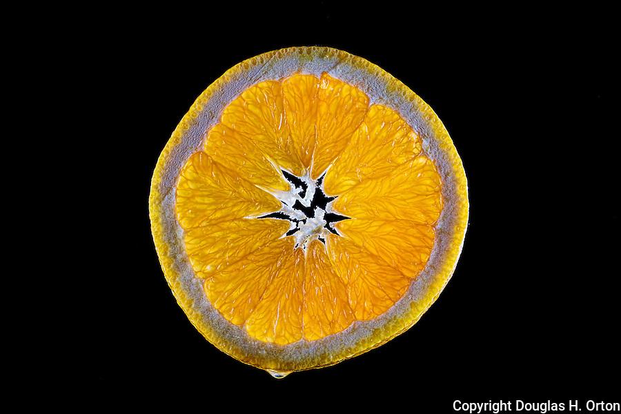 Orange slice backlit on black background.