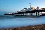 Great Britain, England, East Sussex, Brighton: Stormy sea beneath Brighton Pier at dusk.