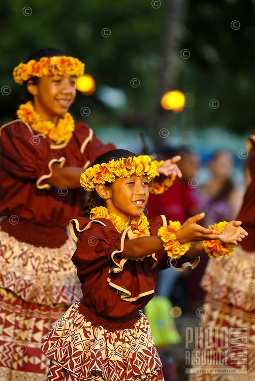 Local keiki (children) wearing head ( haku ) and neck lei made of yellow and orange ilima flowers during an auwana hula performance on the beach at Waikiki. Hula is a Hawaiian form of communication.
