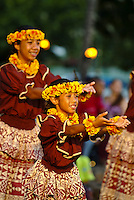 Local keiki (children) wearing head ( haku ) and neck lei made of yellow and orange ilima flowers during an auwana hula performance on the beach at Waikiki. Hula is a Hawaiian form of communication.