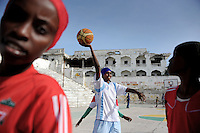 Suweys during practice - Death or Play. Women´s Basketball in Mogadishu.Women's basketball? In Europa and the U.S., we take it for granted. But consider this: In Mogadishu, war-torn capital of Somalia, young women risk their lives every time they show up to play..Suweys, the captain of the Somali women´s basketball team, and her friends play the sport of the deadly enemy, called America. This is why they are on the hit list of the killer commandos of Al Shabaab, a militant islamist group, that has recently formed an alliance with the terrorist group Al Qaeda and control large swathes of Somalia...Al Shabaab, who sets bombs under market stands, blows up cinemas, and stones women, has declared the female basketball players ?un-islamic?. One of the proposed punishments is to saw off their right hands and left feet. Or simply: shoot them...Suweys´ team trains behind bullet-ridden walls, in the ruins of the failed city of Mogadishu - protected by heavily armed gun-men. The women live in constant fear of the islamist killer commandos. Stop playing basketball? Never, they say..Women´s basketball in the world´s most dangerous capital..