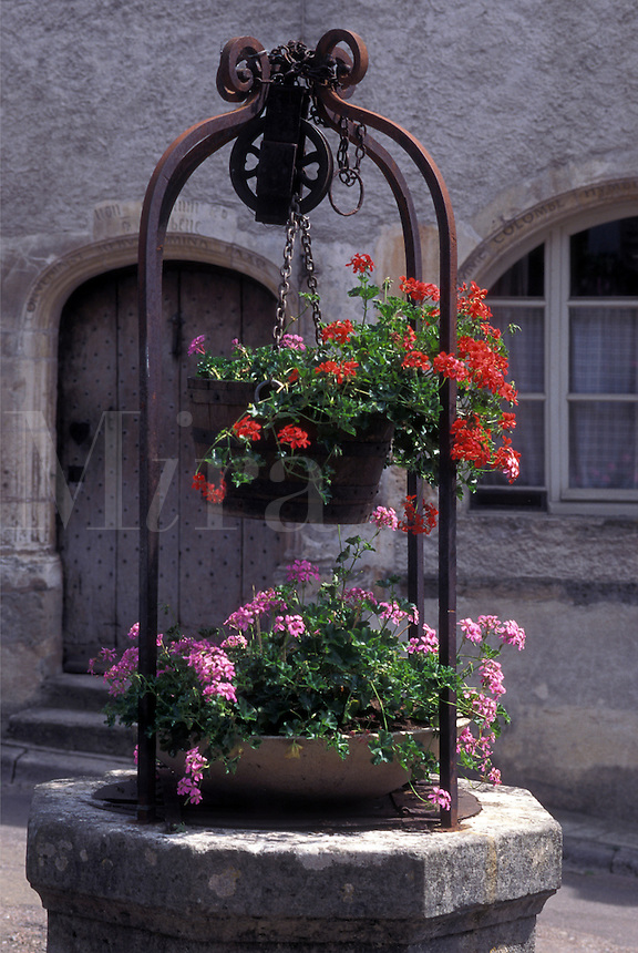 France, Vezelay, Burgundy, Yonne, wine region, Bourgogne, Europe, Old fountain decorated with pink and red geraniums in Vezelay in the wine region of Burgundy.