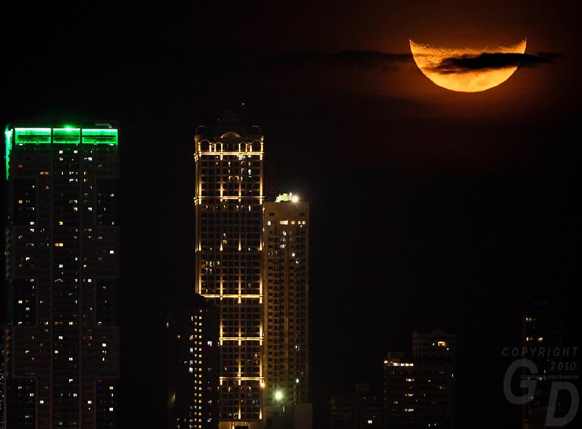 Manila, Philippines Large crest moon, half moon over buildings in Manila, Philippines