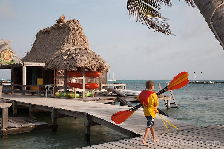 A boy carried kayak paddles toward the activity pier at Ramon's Village Resort in San Pedro, Ambergris Caye, Belize