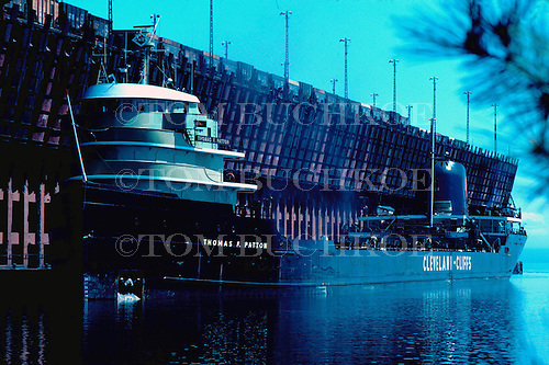 M/V Thomas F Patton, part of the Cleveland-Cliffs Iron Company fleet, awaits a load of iron ore pellets at the LS&I ore dock in Marquette Michigan's upper harbor on Lake Superior. Circa 1970's