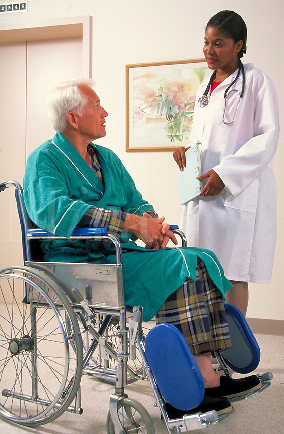 Senior caucasian man in wheelchair in hospital lobby discusses treatment with African-American female doctor. woman doctor and patient.