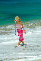 Young woman walking on Makaha beach in a pink sarong on a sunny day with blue ocean in rear