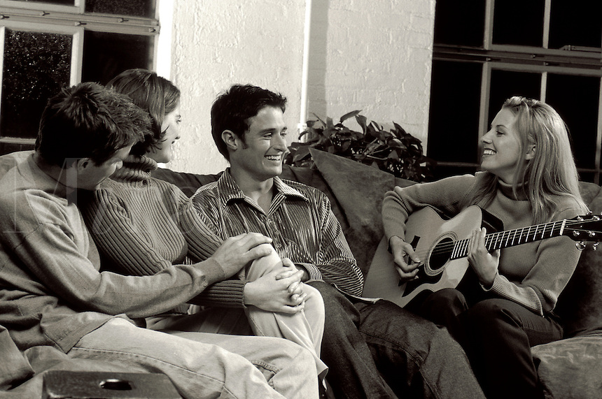 Smiling young couples socializing while playing the guitar.