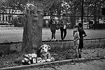 BROOKLYN, NY — JULY 13, 2021:  Children take a break from playing to look at a memorial for 1 year-old Davell Gardner, Jr., who was shot while sitting in his stroller at a barbecue a year ago today, at Raymond Bush Playground in Brooklyn, NY on July 13, 2021. Two suspects were charged in May, in what investigators believe to be part of a feud between rival gangs. Photograph by Michael Nagle