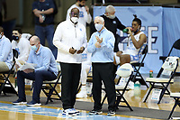 CHAPEL HILL, NC - FEBRUARY 24: Head coach Roy Williams of North Carolina talks with his assistant coach Steve Robinson during a game between Marquette and North Carolina at Dean E. Smith Center on February 24, 2021 in Chapel Hill, North Carolina.