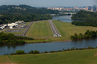 aerial photograph of a Cessna landing on runway 26 at the Knoxville Downtown Island Airport (DXX),  Dickinson Island, Knox County, Tennessee; the skyline of downtown Knoxville is visible in the background