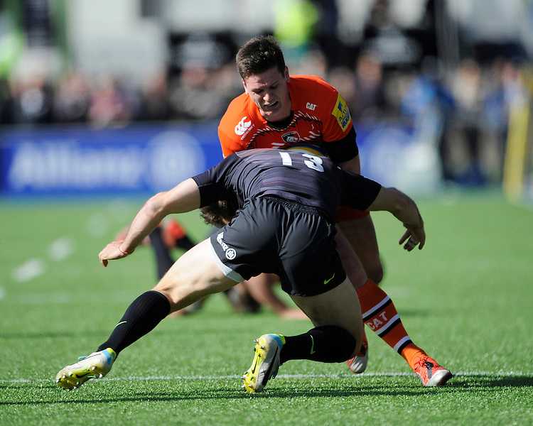 Freddie Burns of Leicester Tigers is tackled by Marcelo Bosch of Saracens during the Aviva Premiership Rugby match between Saracens and Leicester Tigers at Allianz Park on Saturday 11th April 2015 (Photo by Rob Munro)