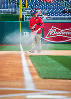7 April 2016: A member of the Grounds Crew spays water on the infield dirt prior to the Washington Nationals Home Opening Game against the Miami Marlins at Nationals Park in Washington, DC. The Marlins defeated the Nationals 6-4 in their first meeting of the 2016 MLB season. Mandatory Credit: Ed Wolfstein Photo *** RAW (NEF) Image File Available ***