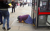 Woman begging in Moorgate, City of London while a man carrying bananas walks by.<br />