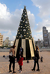 Lebanese people stand beside a Christmas tree with names of those who died during Beirut port explosion, is seen near the damaged grain silo, in Beirut, Lebanon December 22, 2020. Photo by Haitham Moussawi