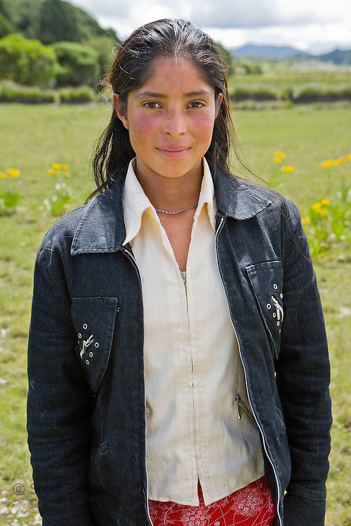 A Guatemalan teenage girl poses in a meadow, outside a church in San Nicolas, Western Highlands, Guatemala