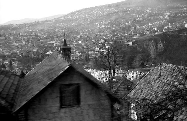 BOSNIA-HERZEGOVINA, Belgrade-Sarajevo Road, 03/2003..The bus overhangs Sarajevo, his white muslim cemeteries and the minarets of the mosques. 200000 persons died during the war between 1992 and 1995.  .BOSNIE-HERZEGONVINE, Route Belgrade-Sarajevo, 03/2003..Photo prise depuis le bus qui relie Belgrade à Sarajevo. Le bus surplombe Sarajevo, son cimetière musulman blanc et les minarets des mosquées. 200000 personnes sont mortes pendant le siège de la ville entre 1992 et 1995..© Bruno Cogez