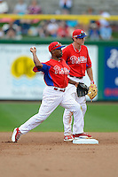 Philadelphia Phillies shortstop Jimmy Rollins #11 turns a double play as Chase Utley #26 looks on during a Spring Training game against the Boston Red Sox at Bright House Field on March 24, 2013 in Clearwater, Florida.  Boston defeated Philadelphia 7-6.  (Mike Janes/Four Seam Images)
