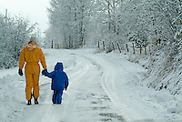 Mother and her three year old daughter walking along a snowy road, Selonnet, French Alps, France.
