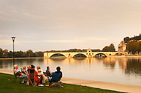 A family group of people having a picnic on the grass in front of the Rhone river overlooking the famous Pont d'Avignon Saint Benezet Bridge, half ruined. Avignon, Vaucluse, Provence, Alpes Cote d Azur, France, Europe
