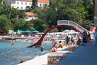 Beach with crowds of tourists and an arched water slide. Uvala Sumartin bay between Babin Kuk and Lapad peninsulas. Dubrovnik, new city. Dalmatian Coast, Croatia, Europe.