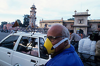 INDIA Rajasthan Jaipur, motorbike driver with mask to protect breathing of exhaust fume at street / INDIEN Jaipur, Motorradfahrer mit Atemschutzmaske zum Schutz vor Abgasen