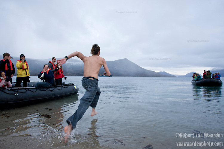 A teenage boy braves the Arctic waters of Qikiqtarjuaq, Nunavut, Canada, for a polar bear swim. He is a member of the Cape Farewell Youth Expedition that was organized by the British Council of Canada.